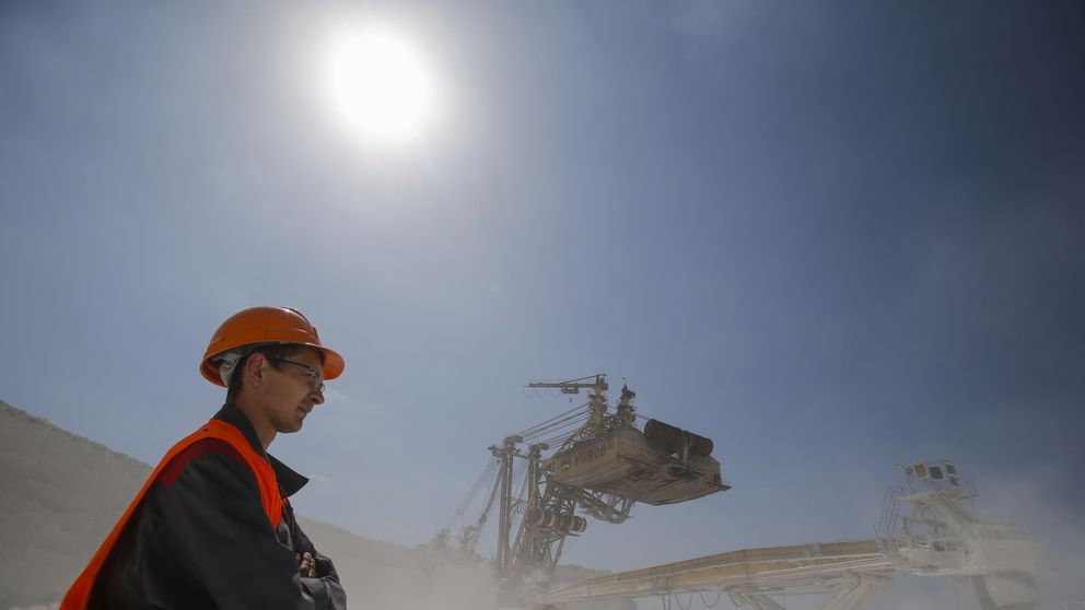 An employee stands near a rotary dredge working at an open-cast iron ore mine of the Stoilensky mining and concentration plant (GOK), owned by the Novolipetsk (NLMK) steel mill, in the city of Stary Oskol in Belgorod region, Russia, August 4, 2015