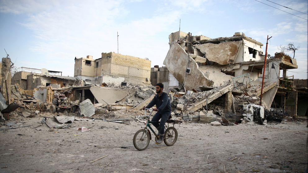A young man rides bicycle near damaged houses in the besieged town of Douma
