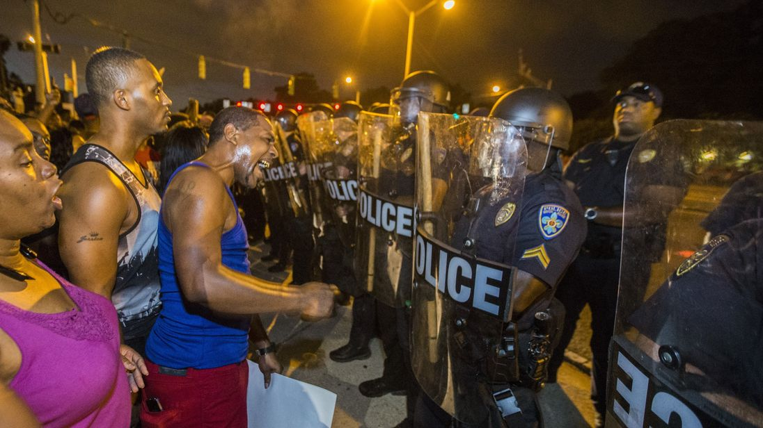 Protesters face off with Baton Rouge police in riot gear across the street from the police department on July 8, 2016 in Baton Rouge, Louisiana