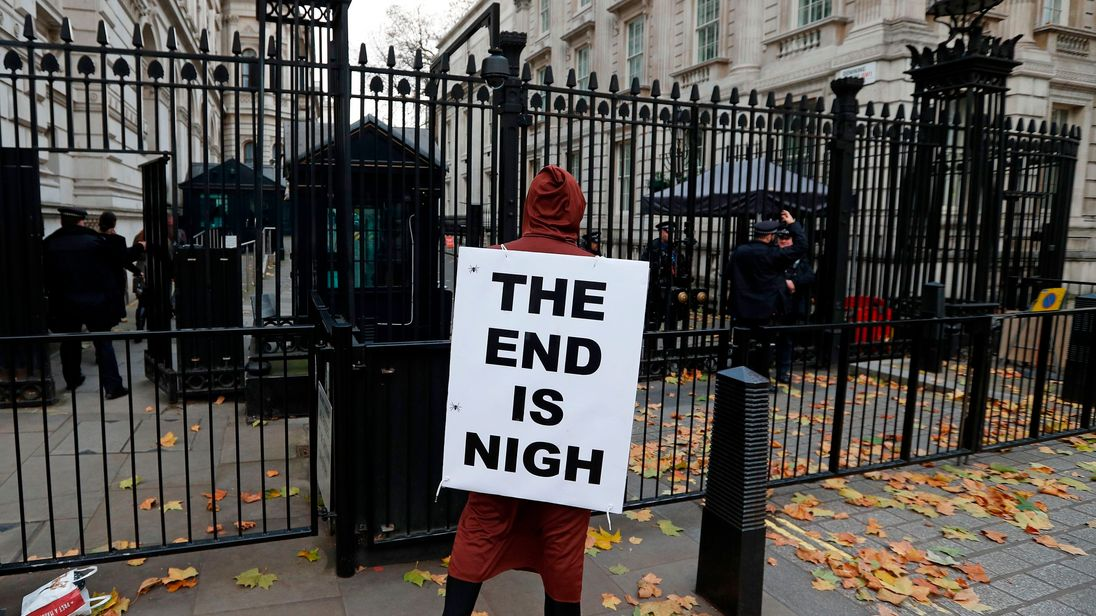 A demonstrator wears a placard as he protests outside the entrance to Downing Street in London, on November 22, 2017, before Britain's Chancellor of the Exchequer Philip Hammond presents the government's annual Autumn budget to Parliament