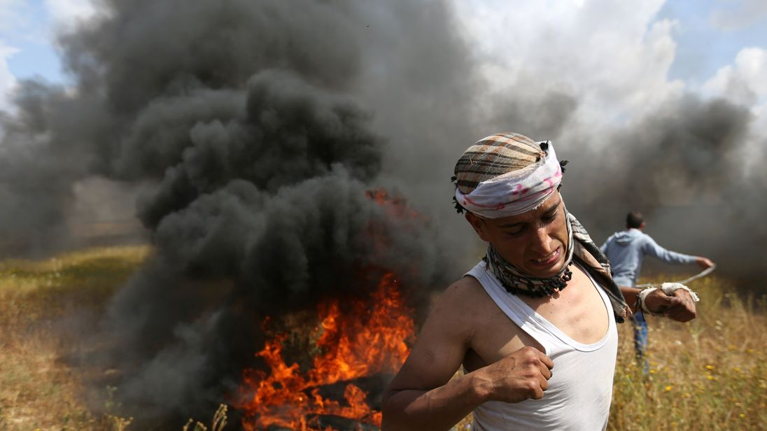 A Palestinian runs during clashes with Israeli troops