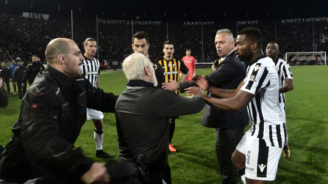 Paok president Ivan Savvidis takes to the pitch carrying a handgun in his waistband