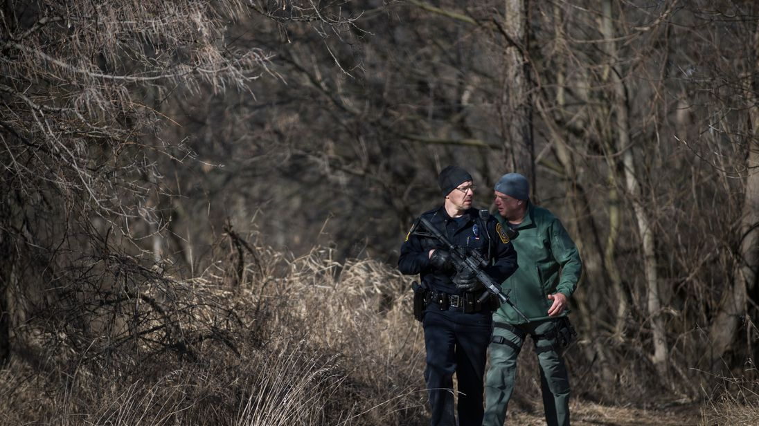 Michigan police officials walk out of the woods as police continue to search for a suspect near Central Michigan University on March 2, 2018 in Mount Pleasant, Michigan