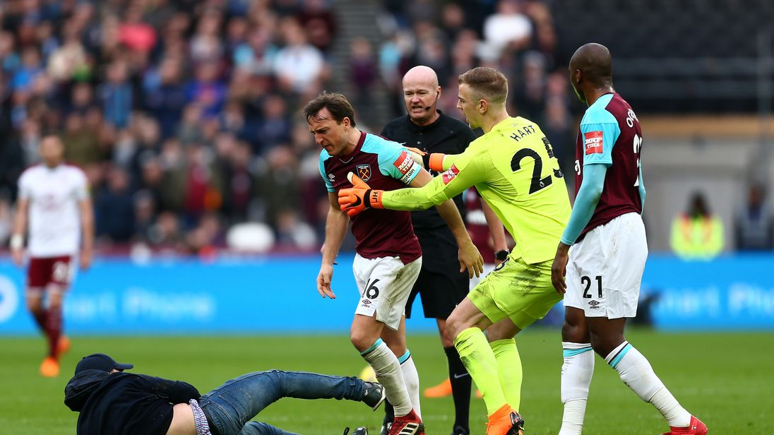 Joe Hart pulls back Mark Noble as a fan invades the pitch