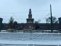 A snow-covered sidewalk in front of Sforzesco Castle in Milan