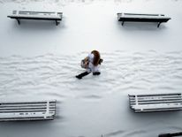 A woman walks past snow covered benches in a park in Lausanne, Switzerland