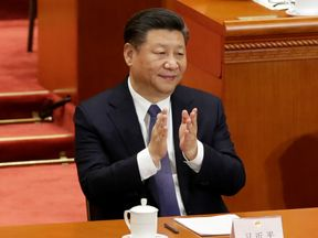 Chinese President Xi Jinping applauds after the parliament passed a constitutional amendment lifting presidential term limit