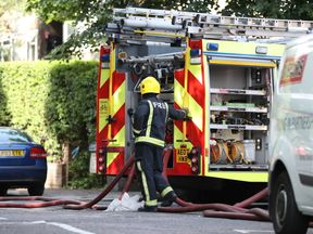 A firefighter next to an appliance in Grenfell Road,