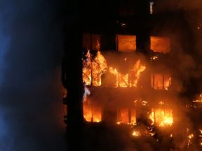 Flames and smoke engulf Grenfell Tower, a residential block on June 14, 2017 in west London. The massive fire ripped through the 27-storey apartment block in west London in the early hours of Wednesday, trapping residents inside as 200 firefighters battled the blaze. Police and fire services attempted to evacuate the concrete block and said 'a number of people are being treated for a range of injuries', including at least two for smoke inhalation. / AFP PHOTO / Daniel LEAL-