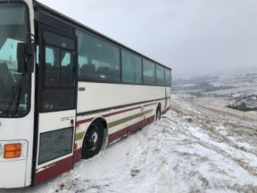 A stranded coach in Littleborough, Greater Manchester, dangling precariously close to the edge of a moorland hill
