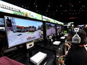 Gamers in the Microsoft Xbox exhibit play the 'Minecraft' game at the Los Angeles Convention center on day one of E3 2017, the three day Electronic Entertainment Expo, one of the biggest events in the gaming industry calendar, in Los Angeles, California on June 13, 2017. / AFP PHOTO / Mark RALSTON (Photo credit should read MARK RALSTON/AFP/Getty Images)