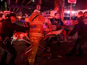 Paramedics and members of the FDNY perform CPR on a victim of a helicopter that crashed into the East River in New York, U.S., March 11, 2018