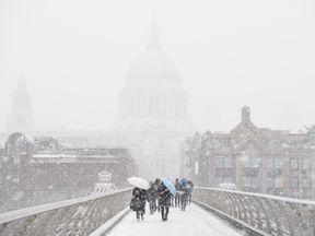 Commuters battle through the blizzard across the River Thames