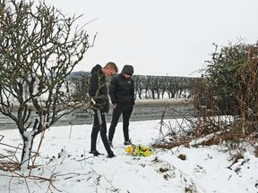 Two youths, aged 17 and 18, look at flowers at the scene on the A61 near Thirsk in North Yorkshire