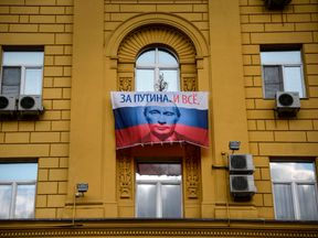 Russian campaign flag depicting Vladimir Putin waving on the balcony of an apartment building in Moscow.