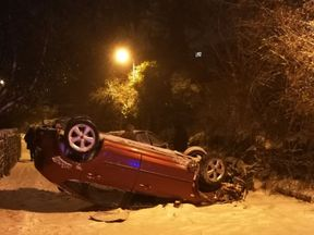 A car on its roof in the snow in west Yorkshire waits to be recovered by police