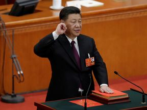 Chinese President Xi Jinping with his hand on the Constitution takes the oath, after he is voted as the president for another term, at the fifth plenary session of the National People's Congress (NPC) at the Great Hall of the People in Beijing, China March 17, 2018. REUTERS/Jason Lee