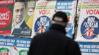 A man stands to look electoral posters in Pomigliano D'Arco, near Naples, Italy, February 21, 2018
