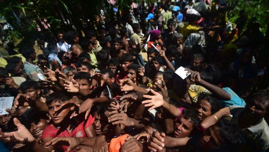 Rohingya refugees scuffle for relief supplies after crossing the Naf River as they flee violence in Myanmar to reach Bangladesh in Palongkhali near Ukhia on October 16, 2017