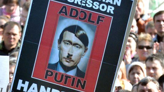 People hold placard portraying Russian President Vladimir Putin as Adolf Hitler