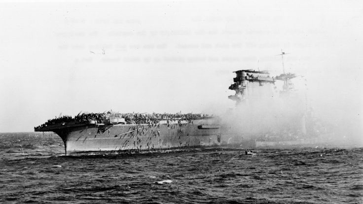 The surviving crew of USS Lexington, sunk by the Japanese in the Coral Sea, abandon ship on 8 may 1942. Sailors slide down ropes and are picked up by small boats; the destroyer (right) is picking up the sick and wounded. (Photo by Hulton Archive/Getty Images)