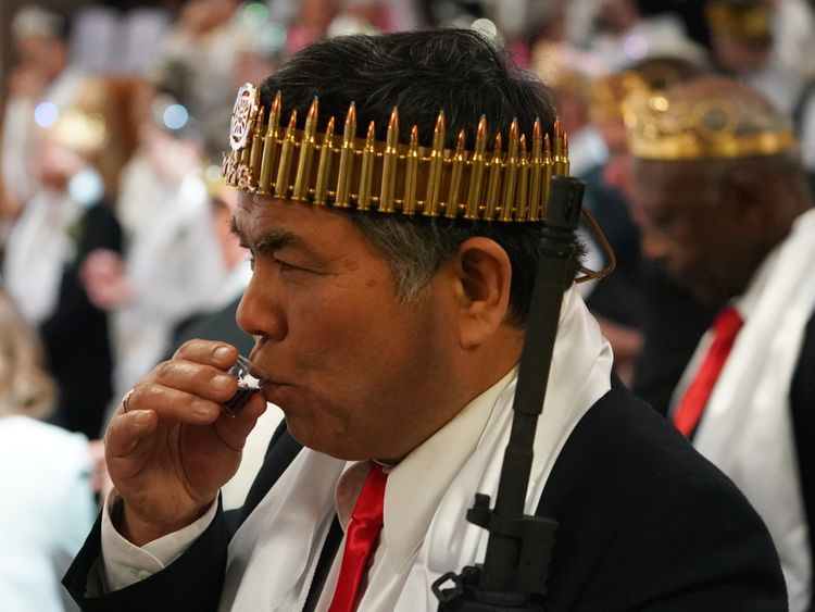 A man wearing a crown of rifle shells takes communion