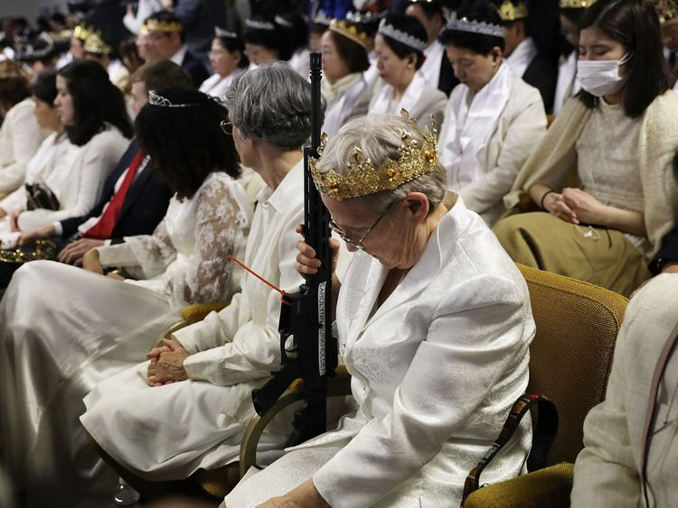 Worshippers at World Peace and Unification Sanctuary hold weapons during their service