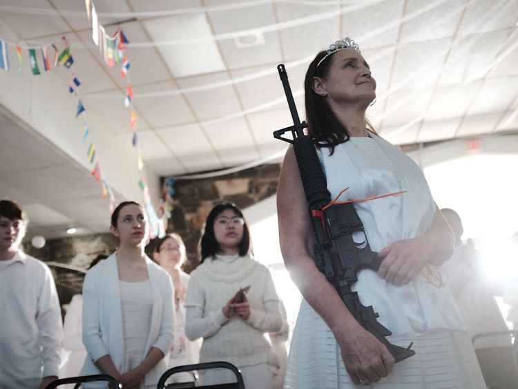 A woman holds an AR-15 rifle during the blessing