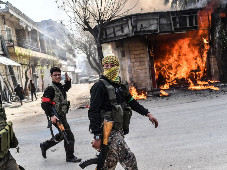 Turkish-backed Syrian rebels walk past a burning shop in Afrin