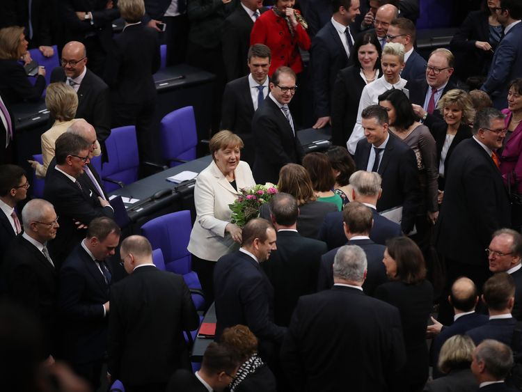 Angela Merkel (in white) receives congratulations from parliamentarians following her election for a fourth term as Chancellor