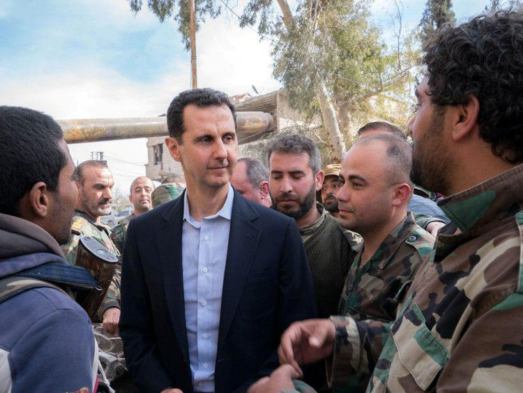 Syrian President Bashar al-Assad walks with Syrian army soldiers in eastern Ghouta