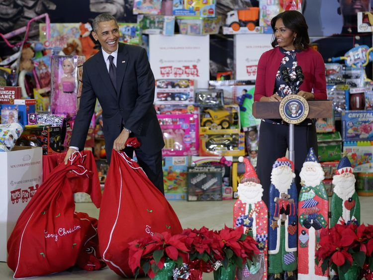 US President Barack Obama (L) sets down bags of toys as he and first lady Michelle Obama deliver gifts donated by Executive Office of the President staff to the Marine Corps Reserve Toys for Tots Program at Joint Base Anacostia-Bolling December 10, 2014 in Washington, DC. For 67 years the Toys for Tots program has worked with local communities to collect and distribute toys and gifts for less fortunate children throughout the United States
