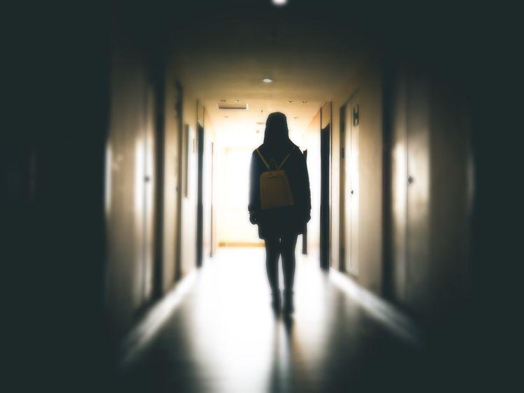 Young woman in dark building walkway - Stock image