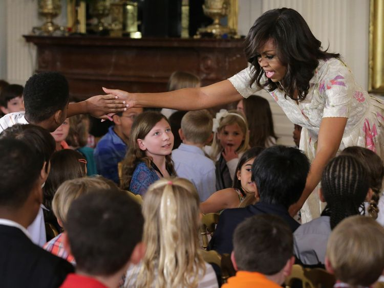 U.S. first lady Michelle Obama gives hugs and high-fives to children for Take Our Daughters and Sons to Work Day in the East Room of the White House April 20, 2016 in Washington, DC