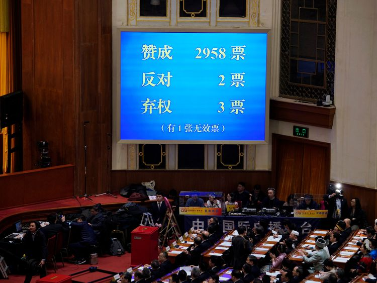 The results of the vote on a constitutional amendment lifting presidential term limits is seen on a giant screen