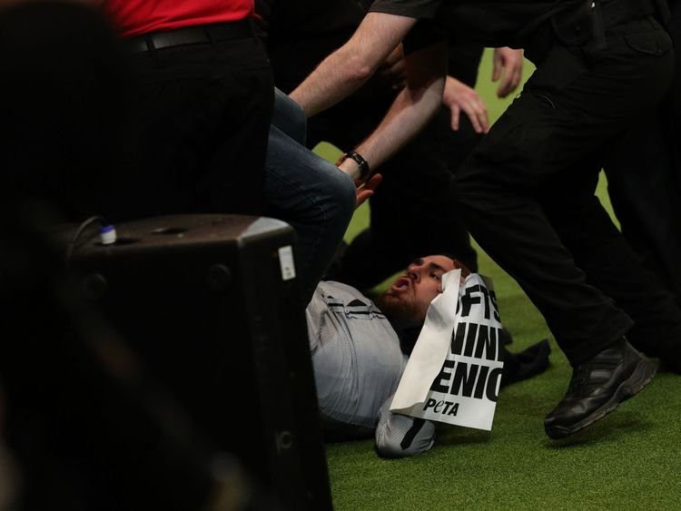 The protester is wrestled to the ground