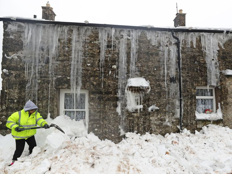 Mags Turnbull from Bowerdale in Cumbria digs herself out after being snowed in for three days