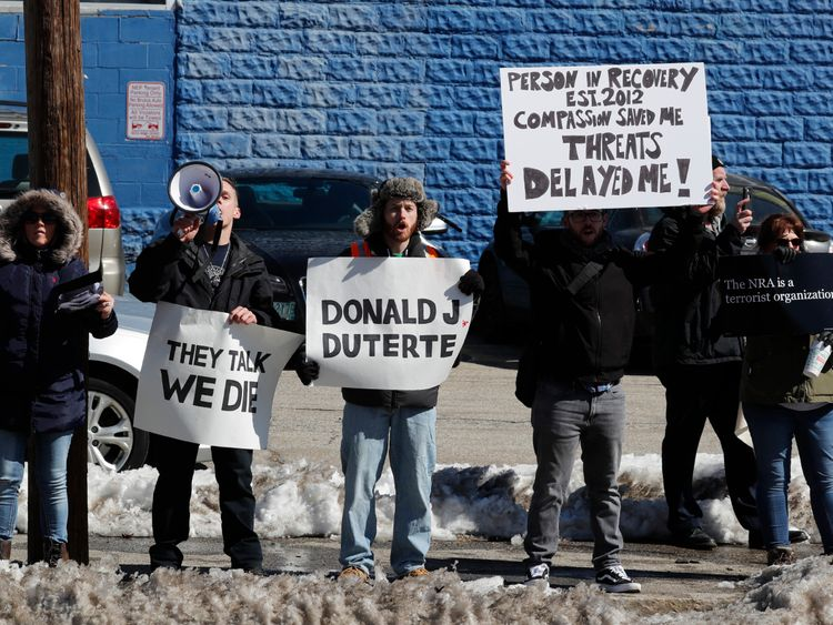 Demonstrators, including one with a sign comparing President Trump to Philippines President Duterte, protest across the street as U.S. President Donald Trump visits a firehouse during a visit to New Hampshire
