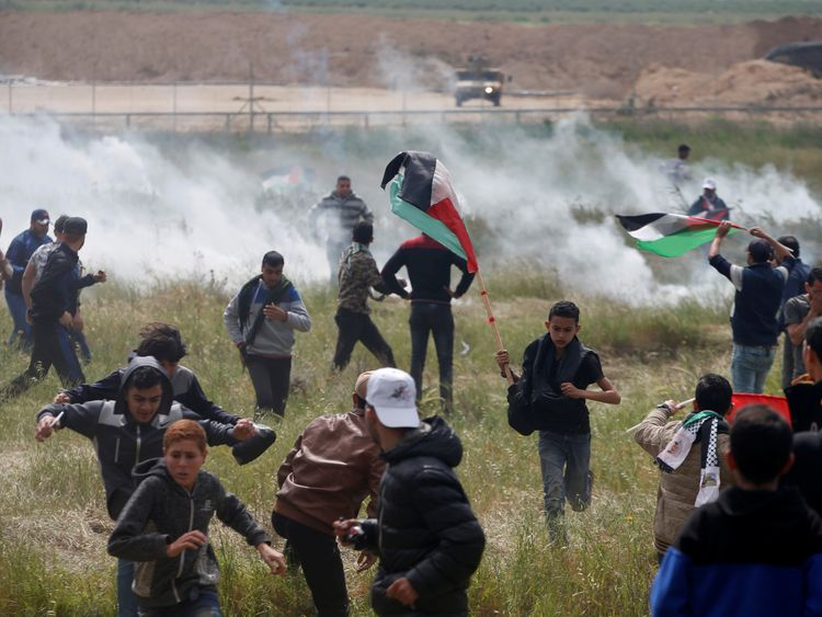Palestinians run from tear gas fired by Israeli troops