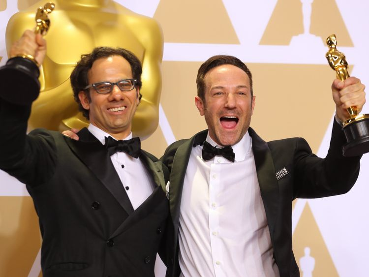 """Dan Cogan (L) and Bryan Fogel pose with their Oscars after winning Best Documentary for """"Icarus"""""""