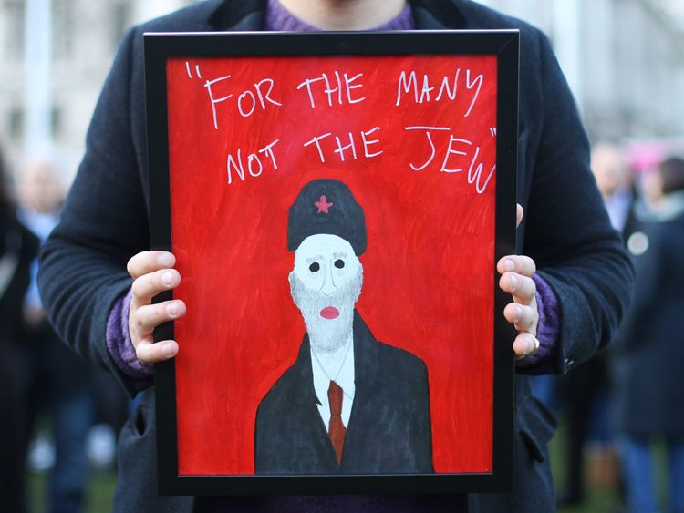 """A demonstrator holding a painting saying """"For the many not the Jew"""""""