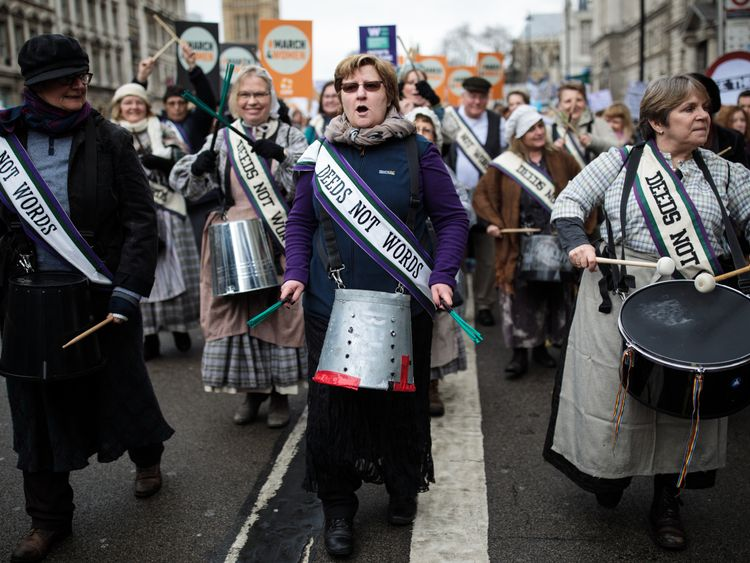 Marchers wore sashes with the suffragettes' famous slogan 'deeds not words'