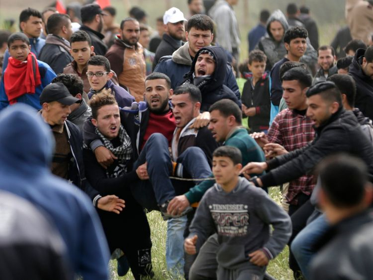 An injured Palestinian youth being carried by other protesters as they flee during clashes