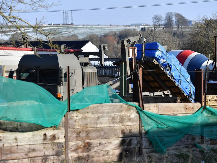 A vehicle covered in a tarpaulin is loaded onto an army vehicle in Durrington, near Salisbury