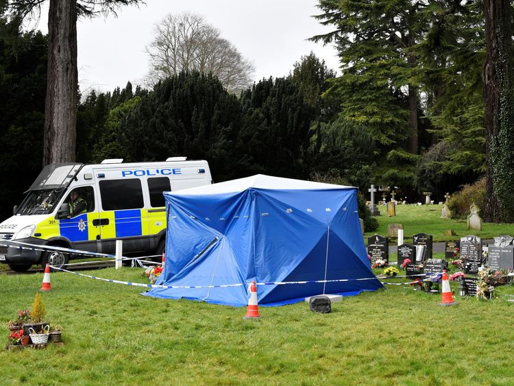 A police van is parked next to a tent covering the headstone of Alexander Skripal; son of former Russian intelligence officer Sergei Skripal in Salisbury