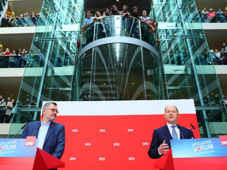 Olaf Scholz (R), interim leader of Germany's Social Democrats (SPD) party, speaks after the SPD's treasurer Dietmar Nietan announced the result