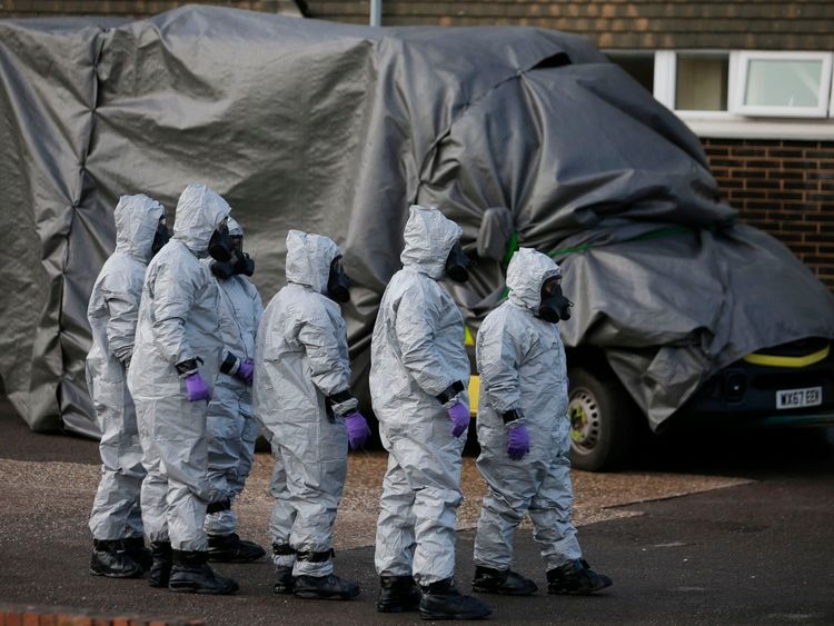 Personnel in protecting coveralls and respirating equiptment cover an ambulance with a tarpaulin at the Salisbury District Hospital in Salisbury, southern England, on Mar 10, 2018