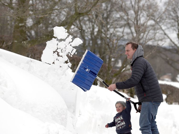 Amelie Muir helps her father Hector clear the snow in their driveway at Blair Drummond, as the cold weather continues around the country