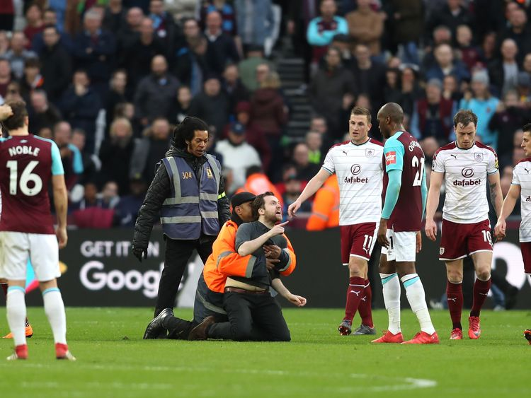 A pitch invader confronts West Ham's Angelo Ogbonna