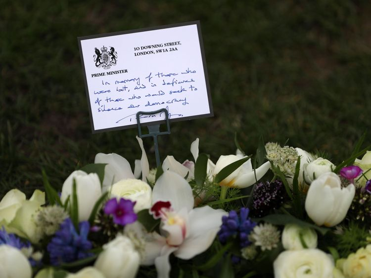 The wreath of white and purple flowers was laid by Theresa May